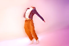 Young modern dancer. Young modern dancer jumping on studio background royalty free stock images
