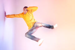 Young modern dancer. Young modern dancer jumping on studio background royalty free stock image