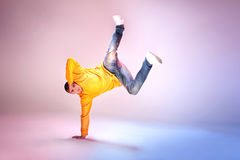 Young modern dancer. Young modern dancer jumping on studio background stock photo