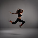 Young modern dancer over grey background Royalty Free Stock Image