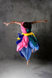 Young modern dancing girl in colorful dress. On the dirty grunge grey studio background stock images