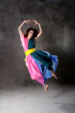 Young modern dancing girl in colorful dress. On the dirty grunge grey studio background royalty free stock photo