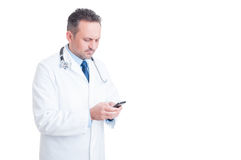 Young and modern doctor or medic texting on smartphone Stock Photo