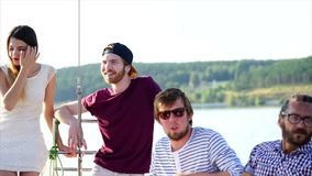 A company of talking friends ride on a sea yacht during the daytime at summer. Young and modern friends ride on a boat during the day, men and women talk about stock video footage