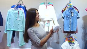 Pregnant woman choosing baby clothing in baby shop. A young modern girl chooses clothes for a newborn baby in a shop, she holds a cap for a newborn stock video
