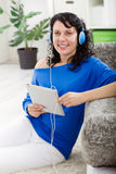 Young modern girl listening to music with electronic tablet Royalty Free Stock Photo