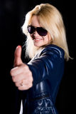 Young modern girl with thumb up against a black background.  Royalty Free Stock Images