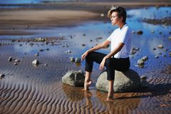 Young modern girl in a white blouse and black pants sitting on a. Rock, dropping his bare feet into the water, and meditates, closing his eyes. Around water Stock Photo