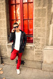 Young modern guy talking on the phone. Red colors Royalty Free Stock Photography