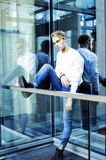 Young modern hipster guy at new building university blond fashio. N hairstyle having fun, lifestyle people concept close up royalty free stock photography