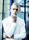 Young modern hipster guy at new building university blond fashio. N hairstyle having fun, lifestyle people concept close up royalty free stock images