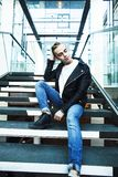 Young modern hipster guy at new building university blond fashio. N handsome boy, lifestyle people concept royalty free stock image