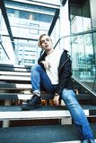 Young modern hipster guy at new building university blond fashio. N handsome boy, lifestyle people concept stock photos