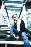 Young modern hipster guy at new building university blond fashio. N handsome boy, lifestyle people concept stock images