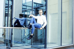 Young modern hipster guy at new building university blond fashion hairstyle having fun, lifestyle people concept. Close up stock image