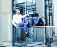 Young modern hipster guy at new building university blond fashion hairstyle having fun, lifestyle people concept. Close up stock photos