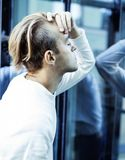 Young modern hipster guy at new building university blond fashion hairstyle having fun, lifestyle people concept. Close up stock photo