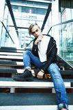 Young modern hipster guy at new building university blond fashio. N handsome boy, lifestyle people concept royalty free stock images