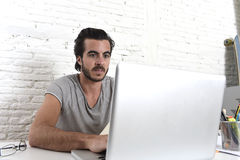 Young modern hipster style student or businessman working with laptop computer at home office Royalty Free Stock Photography