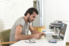 Young modern hipster style student or businessman working with laptop computer at home office writing Royalty Free Stock Images