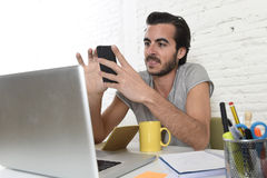 Young modern hipster style student or businessman working using mobile phone smiling happy Stock Photography
