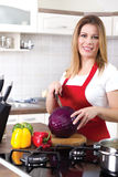 Young modern housewife cuts red cabbage at home Royalty Free Stock Photography