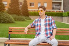 Young guy sitting on bench outdoors. Fashion and urban people co. Young modern looking fashionable man posing by sitting on bench in the park Stock Photography