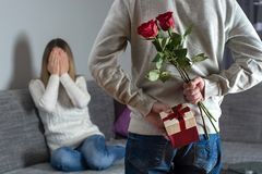 Mans hands hiding holding chic bouquet of red roses and gift with white ribbon behind back and woman with hands over her face awai royalty free stock photography