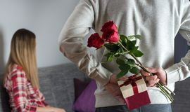 Mans hands hiding holding chic bouquet of red roses and gift with white ribbon behind back and woman with turned head awaits surpr. Young modern male hands stock photo