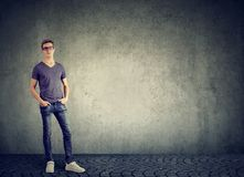 Casual man posing on gray. Young modern man in casual outfit posing with hands in pockets looking at camera on gray Royalty Free Stock Photo