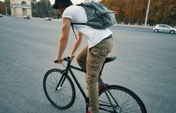 Young modern man cycling on a classic bike on the city road with a backpack stock image