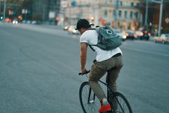 Young modern man cycling on a classic bike on the city road with a backpack stock photo