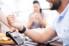 Modern payment. Young modern men with smartwatch making contactless payment over electronic machine after lunch in cafe royalty free stock image