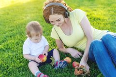 Young modern mom in headphones playing in a green meadow with her cute baby son in a Sunny Park. Joy of motherhood. Beautiful young modern mom in headphones stock photography
