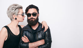 Young modern stylish couple in urban black clothes. Over white background with copy space. Fashion bearded young men and blonde short hair women couple stock images