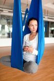 Modern woman. Young modern woman with gadget sitting in swing in gym and practicing aero yoga Royalty Free Stock Images