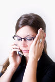 Young modern woman holding cellphone talking. Young woman holds her opposite hear as she talks on a cell phone. It looks as if she is stressed or in Stock Image