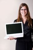 Young modern woman holding laptop smiling. Young modern business woman holding out a laptop computer. Personal text or images can be inserted onto the laptop Royalty Free Stock Photos