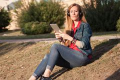 Young modern woman listening to music with headphones and smartphone smiling outdoors in the park royalty free stock photos