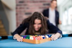 Young modern woman preparing pool balls for the next snooker game royalty free stock photography