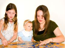 Young Mom and 2 Girls Doing Jigsaw Puzzle Together. A young mom in her 20's is helping a 8 year old girl and baby to do a jigsaw puzzle.  Candid, real life Royalty Free Stock Image