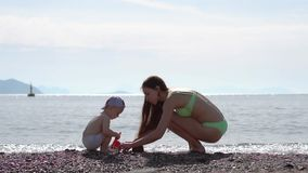 Young mom and baby build sand figures on the beach by the sea in slow motion. Young mom and baby build sand figures on the beach by the sea. Action in slow stock footage