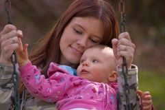 Young Mom and Baby Cuddling on a Swing. This young mom and baby daughter are enjoying a moment of cuddling and snuggling on a swing for a sweet family time Stock Image