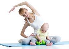 Young mom with baby doing gymnastics and fitness exercises Stock Photo