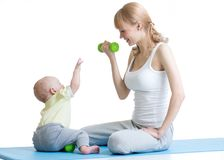 Young mom with baby doing gymnastics and fitness exercises. Isolated on white background Royalty Free Stock Images