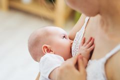 Young mom breast feeding her newborn child. Lactation infant concept. Mother feed her baby son or daughter with breast milk.  royalty free stock photography
