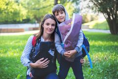 Young mom, carrying newborn in sling, sending her older child at stock photo