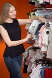 Young mom choosing baby clothes Royalty Free Stock Photography