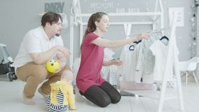 Young mom choosing clothes for cute infant at home stock video footage