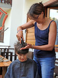 Young mom cuts the hair of her son with the razor at home Royalty Free Stock Image